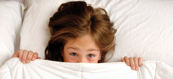 Bang meisje onder haar dekbed